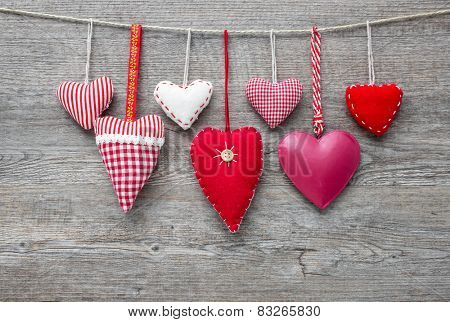 Red hearts hanging on clothesline over grey wood background