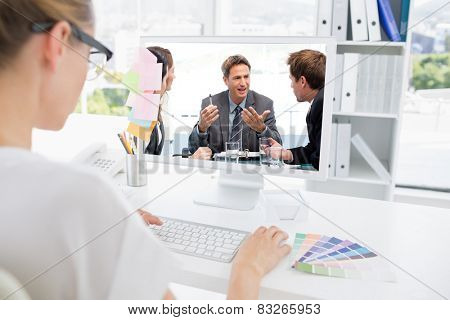 Charismatic chairman talking with his team against rear view of photo editor working on computer