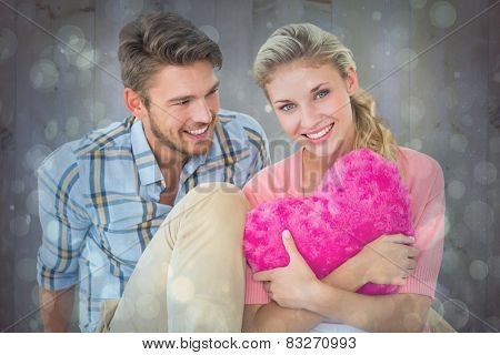 Attractive young couple sitting holding heart cushion against blue abstract light spot design