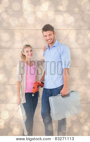 Young couple holding diy tools against light glowing dots design pattern