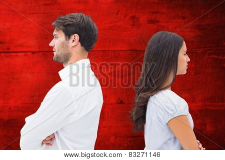 Upset couple not talking to each other after fight against red wooden planks