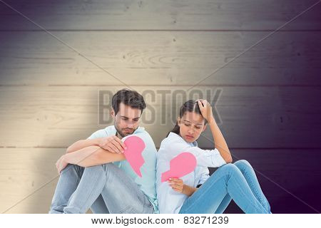 Sad couple sitting holding two halves of broken heart against shadow on wooden boards