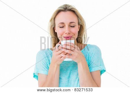 Cheerful blonde holding mug of hot drinking on white background