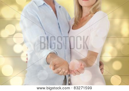 Happy couple holding their hands out against light circles on bright background