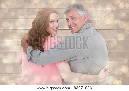 Casual couple standing arms around against light glowing dots design pattern
