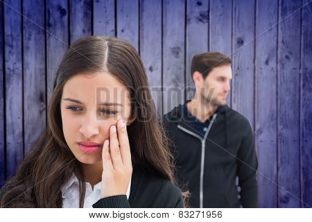 Unhappy couple not speaking to each other against wooden planks background