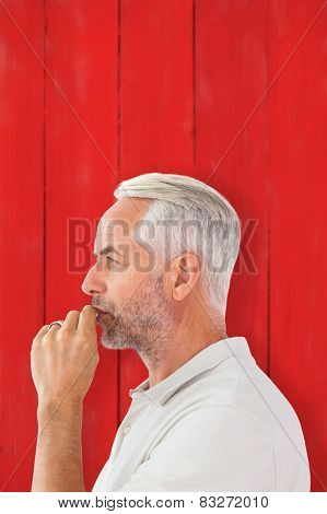 Man staying silent with finger on lips against red wooden planks