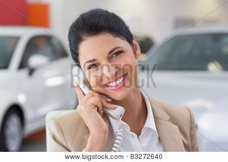 Smiling businessman making a phone call at new car showroom