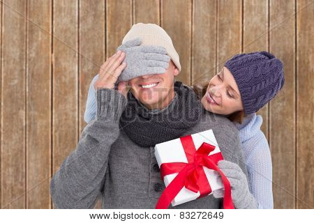 Woman surprising husband with gift against wooden planks