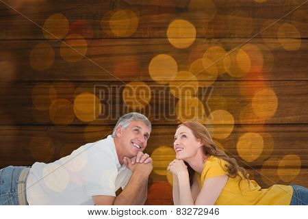 Casual couple lying on floor against close up of christmas lights