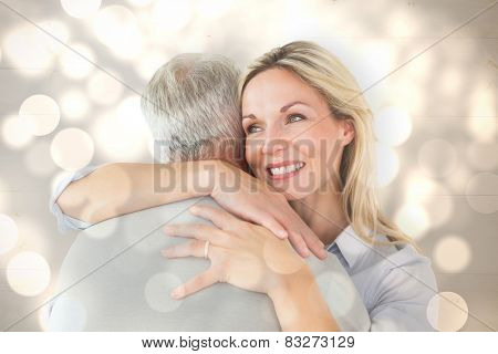 Happy couple standing and hugging against light circles on bright background