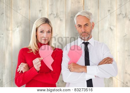 Couple not talking holding two halves of broken heart against pale wooden planks