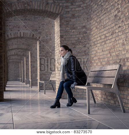 Young woman sitting on a bench, looking into the lost
