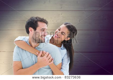 Cute couple smiling at each other against shadow on wooden boards