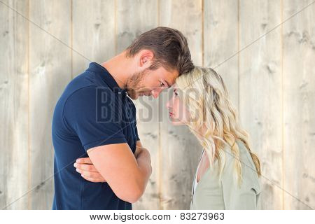 Young couple standing head to head against pale wooden planks