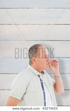 Older man holding hand to mouth for silence against wooden planks
