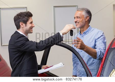 Businessman giving car key while shaking a customer hand at new car showroom