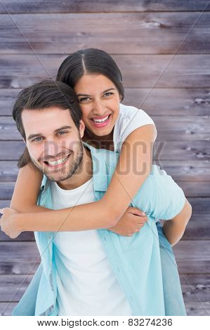 Happy casual man giving pretty girlfriend piggy back against faded grey wooden planks