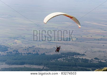 Two men paragliding high above mountain range