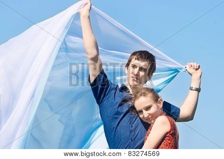 Young Pair With White Scarf Against Blue Sky