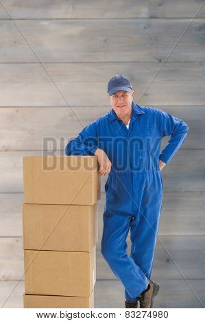 Happy delivery man leaning on pile of cardboard boxes against pale grey wooden planks