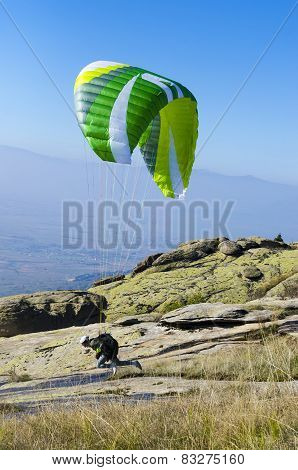 Paraglider preparing to take off from a mountain