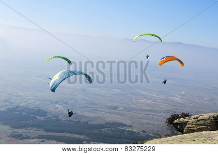 Four paragliders flying above the mountain, extreme sport