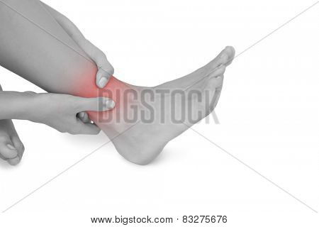 Close up of woman touching her injured foot on white background