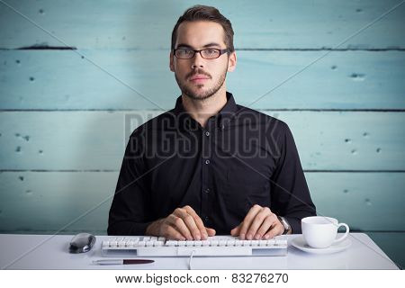 Focused businessman typing on keyboard against painted blue wooden planks