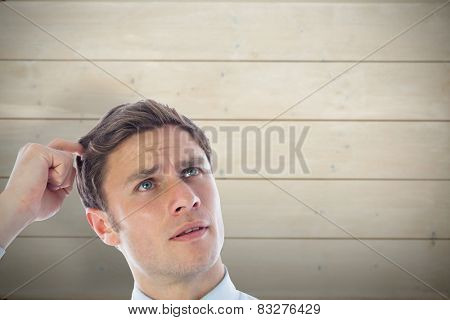 Thinking businessman scratching head against bleached wooden planks background
