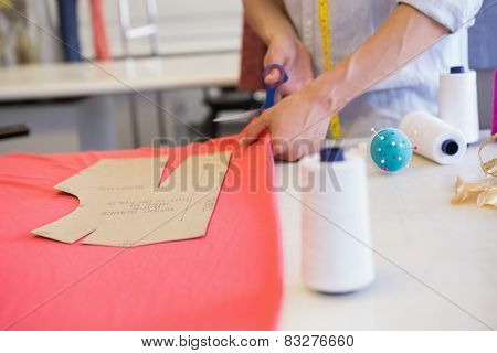 Student cutting fabric with pair of scissors at the college