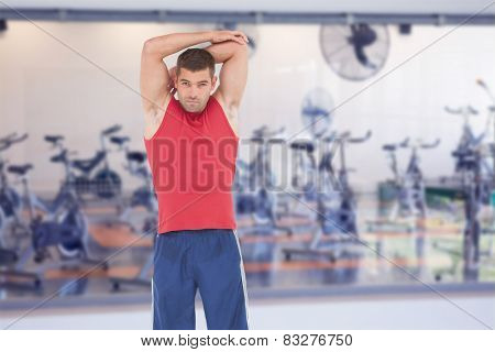 Fit man stretching his arms against empty spin studio with fans