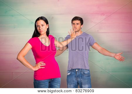 Young couple having an argument against pink and green planks