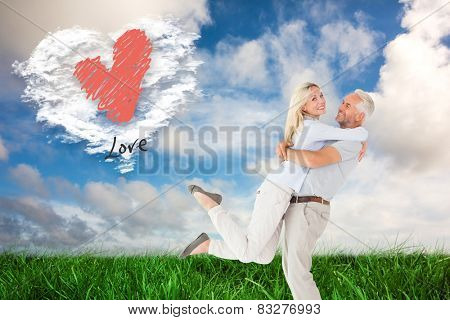Man picking up his partner while hugging here against cloud heart