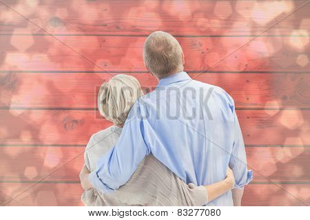 Mature couple hugging and looking against light glowing dots design pattern