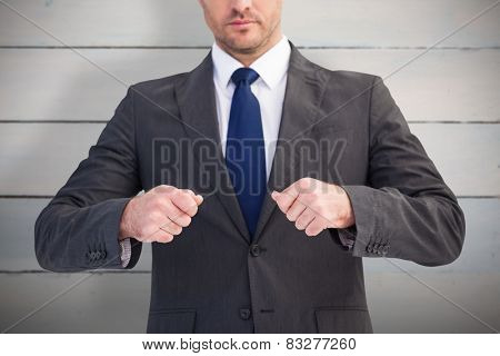 Mid section of a businessman with clenched fist against painted blue wooden planks