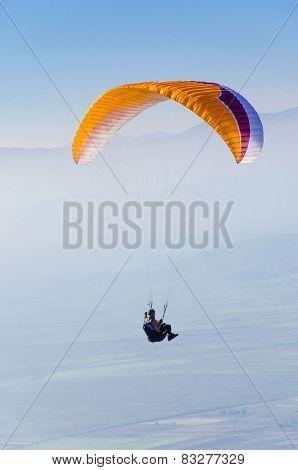 Orange paraglider flying against the blue sky
