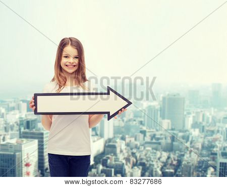 advertising and child concept - smiling little girl with blank arrow pointing right