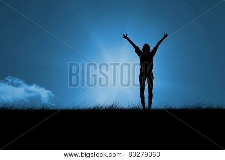 Silhouette of cheering woman against blue sky over grass