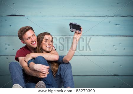 Couple taking selfie with digital camera against painted blue wooden planks
