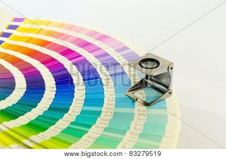 Magnifying glass standing on a color palette