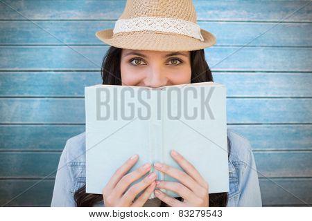 Brunette reading against wooden planks