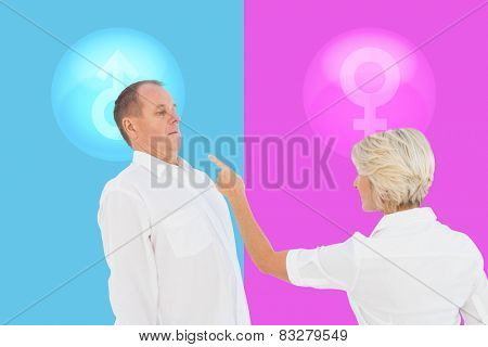 Angry older couple arguing with each other against pink and blue