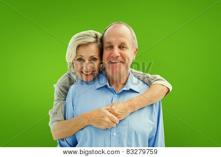 Happy mature couple embracing smiling at camera against green vignette