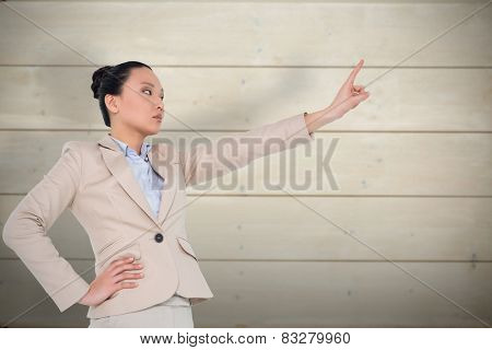 Unsmiling asian businesswoman pointing against bleached wooden planks background