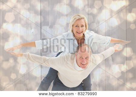 Happy mature couple having fun against light glowing dots design pattern