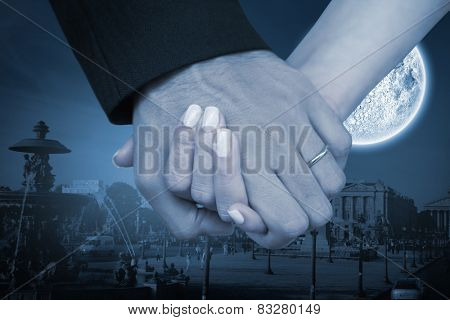 Newlyweds holding hands close up against large moon over city