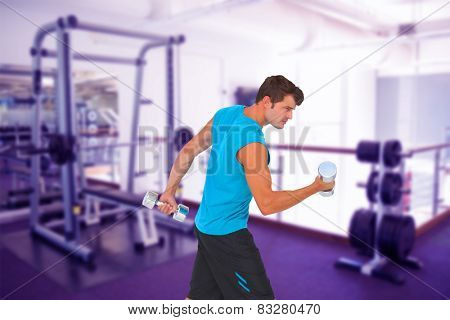 Fit man lifting heavy dumbbells against empty weights room with bench press