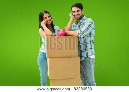 Happy young couple with moving boxes and piggy bank against green vignette
