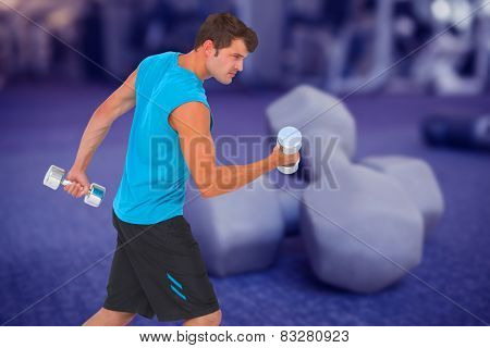 Fit man lifting heavy dumbbells against grey dumbbells on the weights room floor